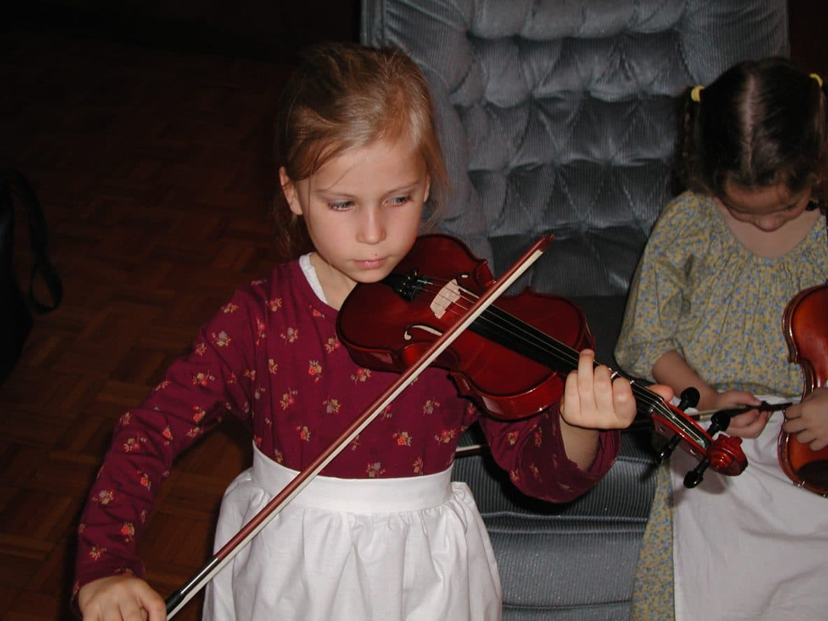 Gaylyn Foto playing violin on Thanksgiving Day while dressed up like a Pilgrim.